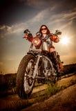 Radfahrermädchen, das auf Motorrad sitzt Lizenzfreie Stockfotografie