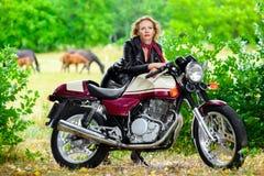 Radfahrermädchen in der Lederjacke auf einem Motorrad vorbei stockbild
