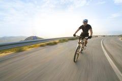 Radfahrermann-Reitmountainbike am sonnigen Tag Lizenzfreie Stockfotos