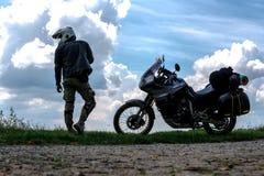 Radfahrermann und -tourist weg vom Straßenmotorrad mit dem Reiter des jungen Mannes der Seitentaschen, zum während der Reise st stockbild