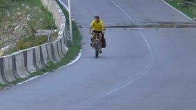 Radfahrerreiten auf einer gepflasterten Straße stock footage