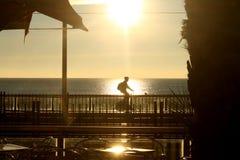 Radfahrerreiten bei dem Sonnenaufgang Stockbild
