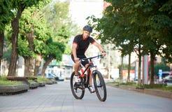 Radfahrerreiten entlang leeren Stadtstraßen Lizenzfreie Stockfotografie