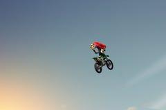 Radfahrerstuntman, der eine Bremsung in der Luft tut Stockbilder
