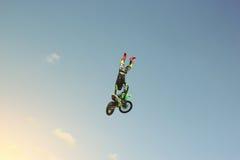 Radfahrerstuntman, der eine Bremsung in der Luft tut Stockfoto