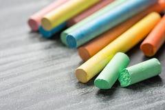 Radhög av mångfärgade Chalksfärgpennor på den mörker skrapade svart tavla Dra tillbaka till hantverk för den grafiska designen fö Arkivfoto