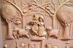 Radha Krishana Mural Wall Art India. Displaying Lord Krishna playing flute. Cows are also seen near it royalty free stock image