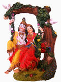 Radha Krishna. A beautiful artifact showing radha and lord Krishna of hindu mythology, sitting on a swing in s garden Royalty Free Stock Photo