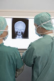 Radiólogos que examinan la radiografía del cráneo Imágenes de archivo libres de regalías