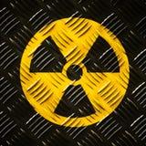 Radiación ionizante radiactiva alrededor del símbolo amarillo y negro del peligro pintado en una pared de acero masiva de la plac imagenes de archivo