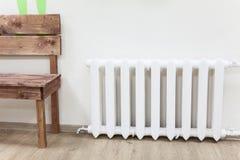 Radiador branco do ferro do aquecimento central perto do banco de madeira na sala Imagens de Stock Royalty Free