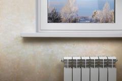 Radiador de aquecimento branco em uma parede leve sob a janela branca imagens de stock royalty free