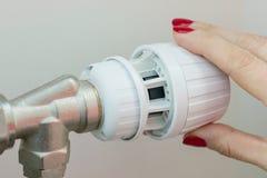 Radiador de la calefacción en un apartamento La mano femenina en el termóstato regula la temperatura foto de archivo