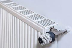Radiador en una pared con el termóstato fotografía de archivo