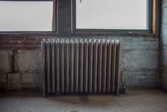 Radiador viejo en el edificio del desván Foto de archivo libre de regalías