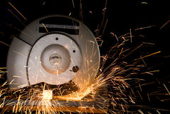 Radial arm saw. A radial arm saw slices through metal square stock, casting a stream of sparks stock photography