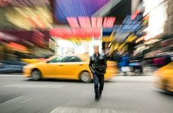 Radial blur of yellow taxicabs and unidentified person in New York City royalty free stock photo