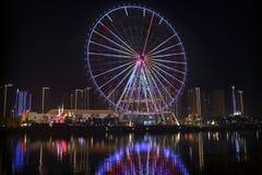 Radiale lichten in de grote wielen, naast de rivier bij nacht Stock Foto