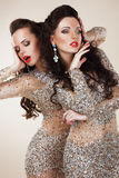 Radiance. Glam. Luxurious Rich Women In Grey Dresses with Rhinestones. Couple of Fashion Young Women In Gray Dresses dancing stock images