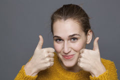 Radiant approval concept for beautiful 20s girl with thumbs up. Radiant approval concept - beautiful 20s girl smiling with thumbs up for satisfaction and royalty free stock photo