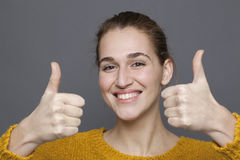 Radiant approval concept,woman. Radiant approval concept - gorgeous 20s girl smiling with double thumbs up for satisfaction and success,studio shot on gray royalty free stock photo