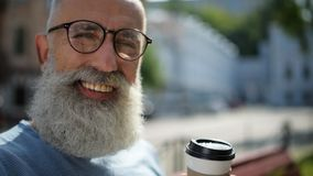 Radiant bearded man with cup of coffee smiling into camera stock footage