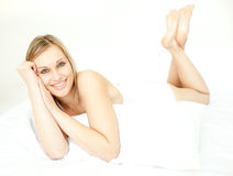 Radiant blond woman lying down on bed. At home stock photography