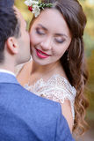 Radiant bride closes her eyes while groom kisses her cheek Stock Photography