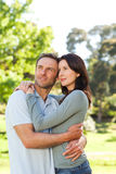 Radiant couple hugging in the park Stock Photos