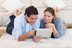 Radiant couple using a tablet computer Stock Photography