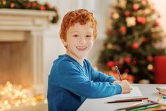 Radiant curly haired child smiling while drawing at home. Next great artist. Waist up shot of a positive minded little boy turning his head into the camera and Stock Image