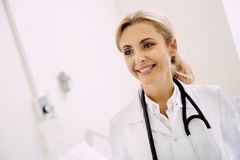 Radiant doctor grinning broadly at hospital Stock Photos