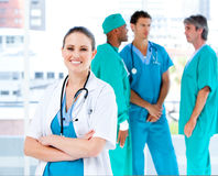 Radiant doctor looking at the camera. Radiant female doctor looking at the camera while her medical partners talking together in the hospital royalty free stock photo