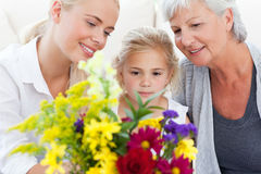 Radiant family with flowers. At home Royalty Free Stock Photos