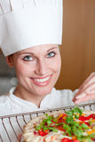 Radiant female chef cooking a pizza Stock Photo
