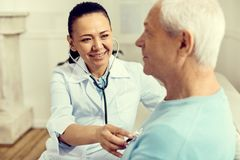 Radiant female nurse using stethoscope while checking lungs. Good results. Selective focus on a happy mature doctor smiling and looking at a retired patient royalty free stock photo
