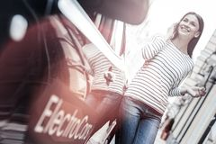Radiant girl having pleasant conversation next to her electric car stock image