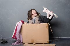 Radiant girl with shaggy hair. Radiant girl in old clothes sitting in a paper box and playing with a used toy, close-up. Hat on the floor, shaggy hair, grey royalty free stock images