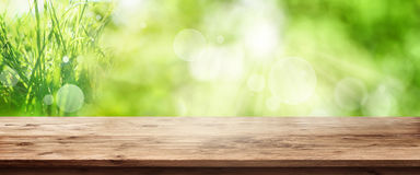 Radiant green spring background with wooden table. Radiant green spring background panorama with grass in front of a wooden table for a concept Stock Photos
