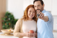 Radiant husband and wife holding keys to new house. Moving house. Selective focus on keys to a new house in hands of a cheerful married couple standing in their Stock Images