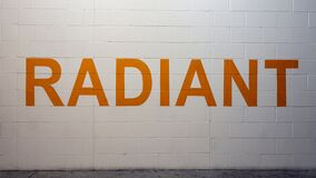 Free RADIANT Is Painted In Bold Orange Letters On A White Brick Wall In The Parking Garage On Victory Park Lane, Dallas, Texas Stock Photo - 177402820