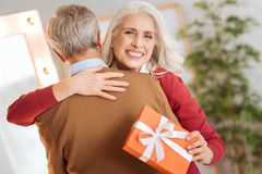 Radiant lady grinning broadly and hugging her husband Royalty Free Stock Photos