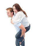 Radiant man giving his girl friend piggyback ride Stock Photography