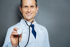Radiant medical worker with stethoscope beaming into camera. Early prevention. Portrait of a mature medical professional using his stethoscope while posing into stock images