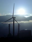 Radiant morning sun behind power plant and windmill Royalty Free Stock Photos