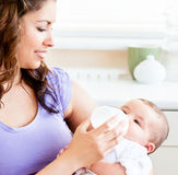 Radiant mother feeding her adorable son at home. Radiant mother feeding her adorable son in the kitchen at home royalty free stock photos