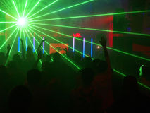 Radiant party. Silhouettes dancing in the night club against the radiant laser show Royalty Free Stock Images