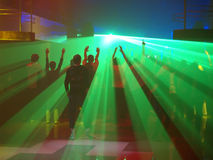 Radiant party. Silhouettes dancing in the night club against the radiant laser show royalty free stock photography