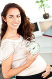 Radiant pregnant businesswoman holding alarm clock Royalty Free Stock Photography