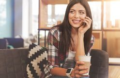 Radiant pretty lady having phone conversation while drinking coffee Stock Images